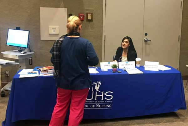 Aya Almukhtar, an AUHS Admissions Coordinator, speaking to a prospective student at Cedars-Sinai's BSN/MSN Education Fair.