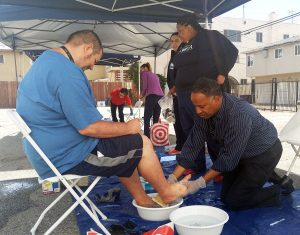 Pastor Gregory Johnson, the Co-founder of AUHS, washes the first guest's feet at the annual Lamp Unto My Feet on Thursday, April 13, 2017.