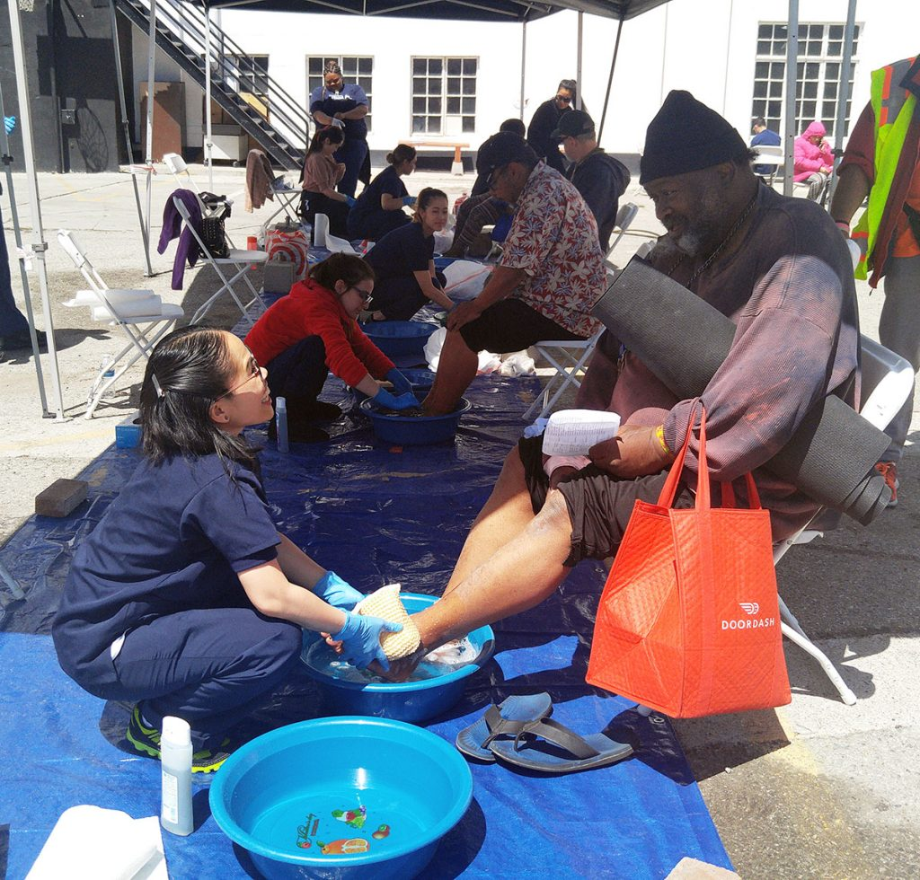 Robert Lee gets his feet washed by an AUHS student at the annual Lamp Unto My Feet event on Thursday, April 13, 2017.